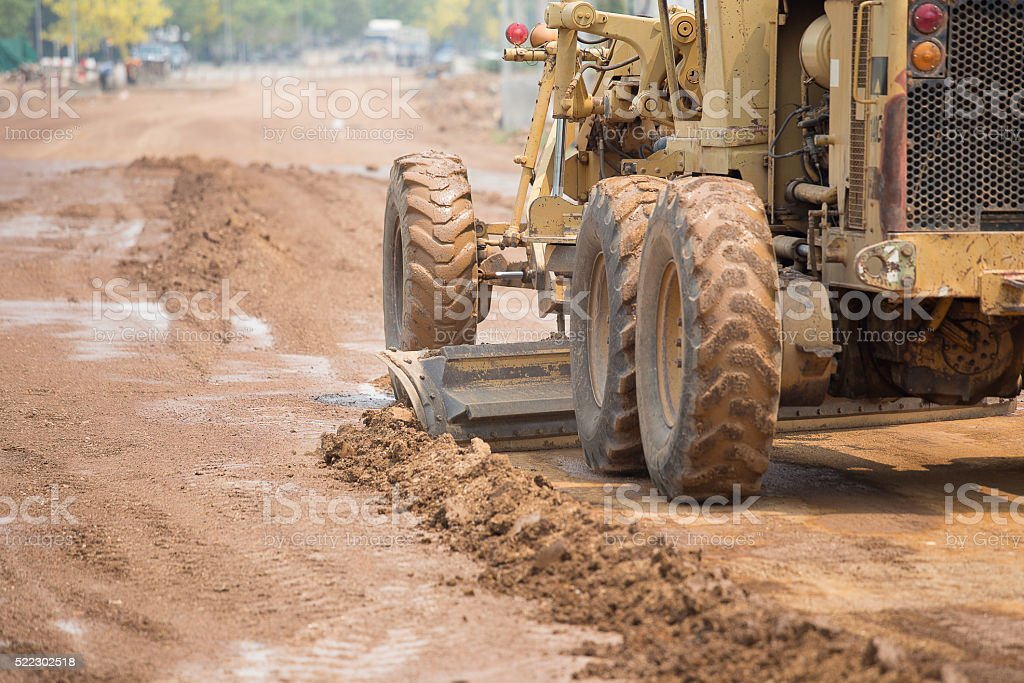 road grader at work on road construction site stock photo