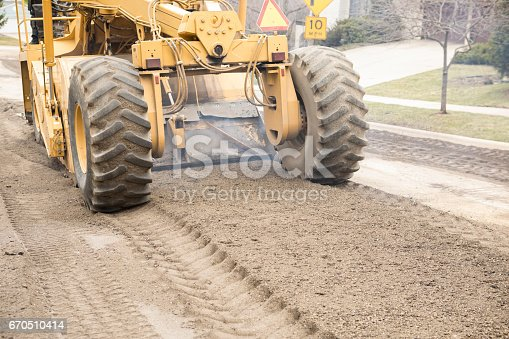 A road grader (road scraper, motor grader) is leveling a crushed rock base for new pavement on a residential street.