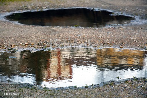 Road in bad conditions, row of buildings reflected on a pothole. Galicia, Spain.