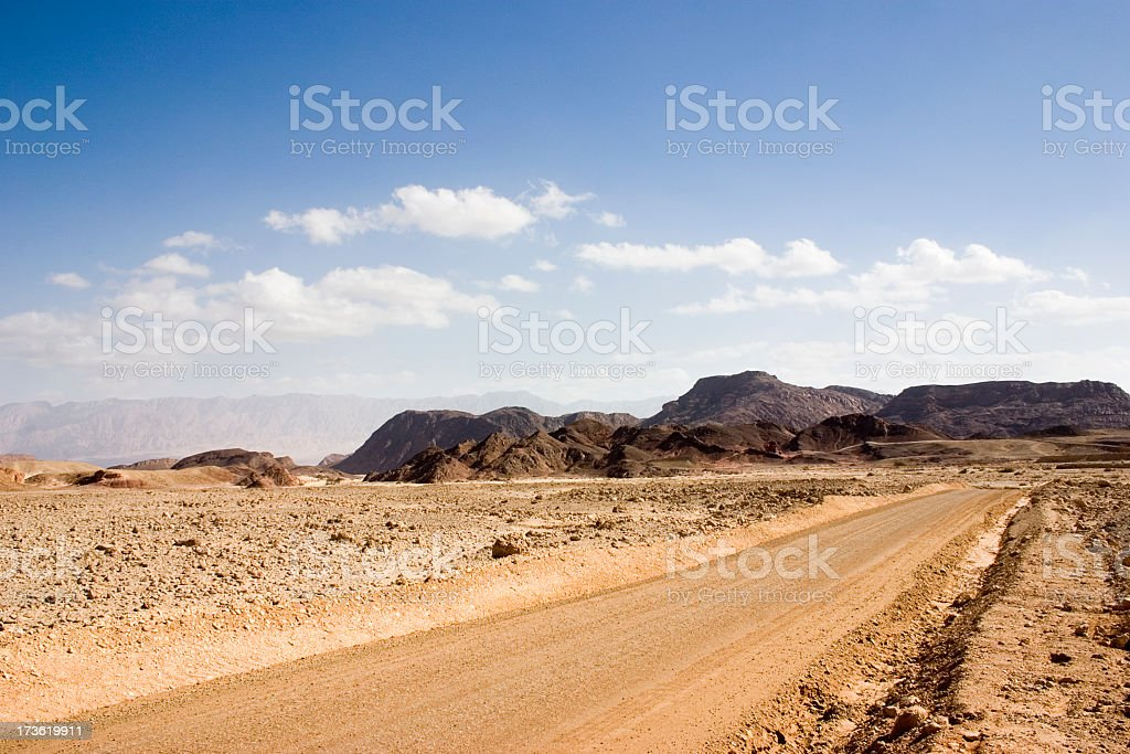 Road in desert leading to mountains with blue sky and clouds stock photo