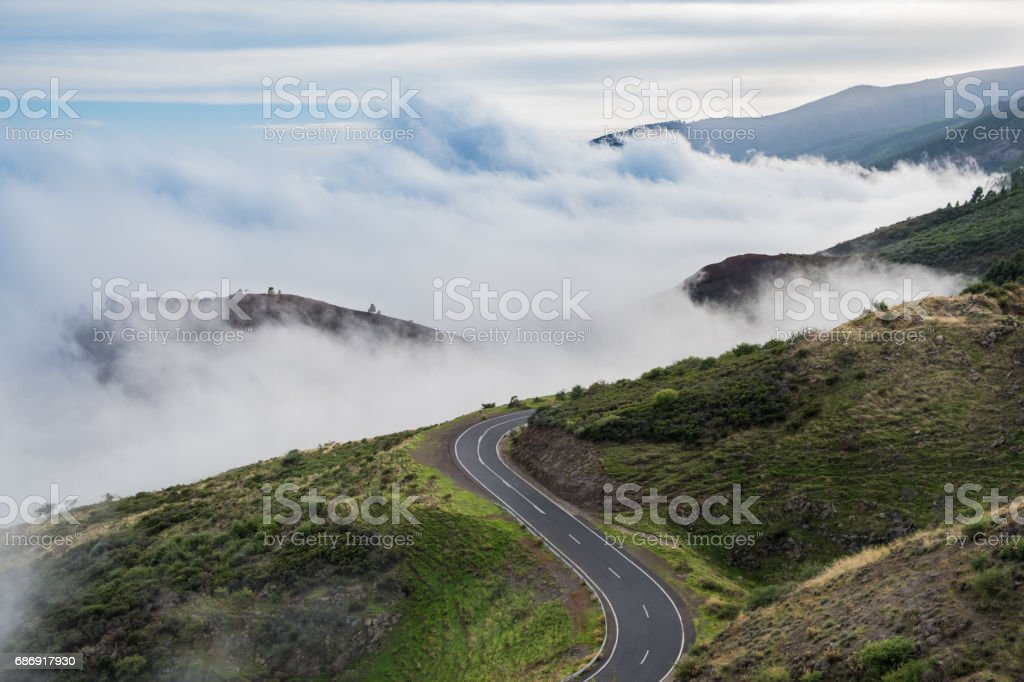 road in mountain landscape over clouds stock photo