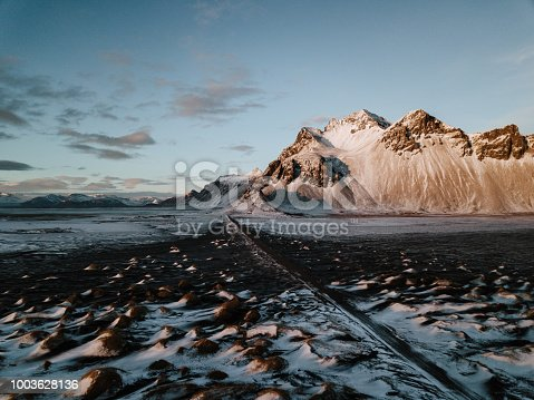 A road leading towards a mountain through a snow covered landscape in Stokksnes, Iceland. The photo is taken using a drone.