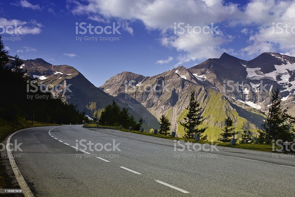 Road in the Alpine with mountains in background  stock photo