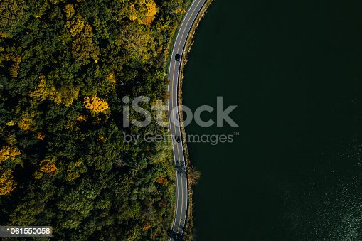 1061550162 istock photo Road in the autumn forest aerial view with lake 1061550056