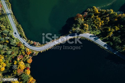 1061550162 istock photo Road in the autumn forest aerial view with lake 1061550068
