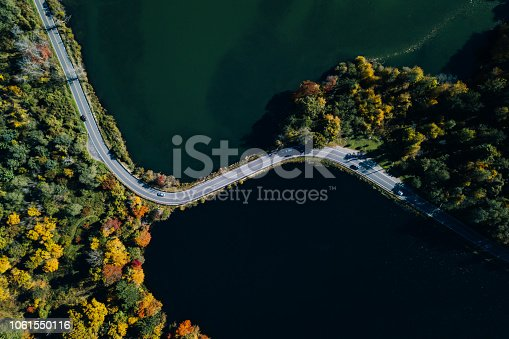 1061550162 istock photo Road in the autumn forest aerial view with lake 1061550116