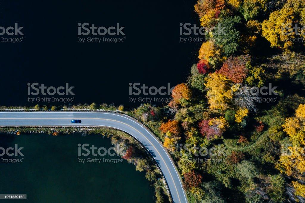 Straße in den herbstlichen Wald Luftbild mit See – Foto