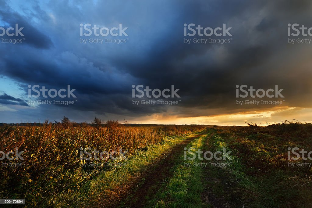 Road in the field and the dark dramatic rain clouds. stock photo