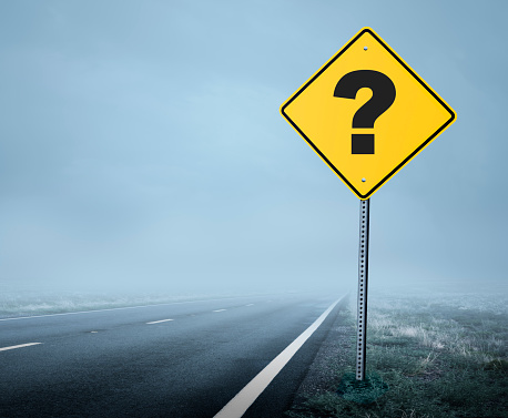 A road sign with a question mark on it on a road shrouded in fog and mist that leads toward the unknown.