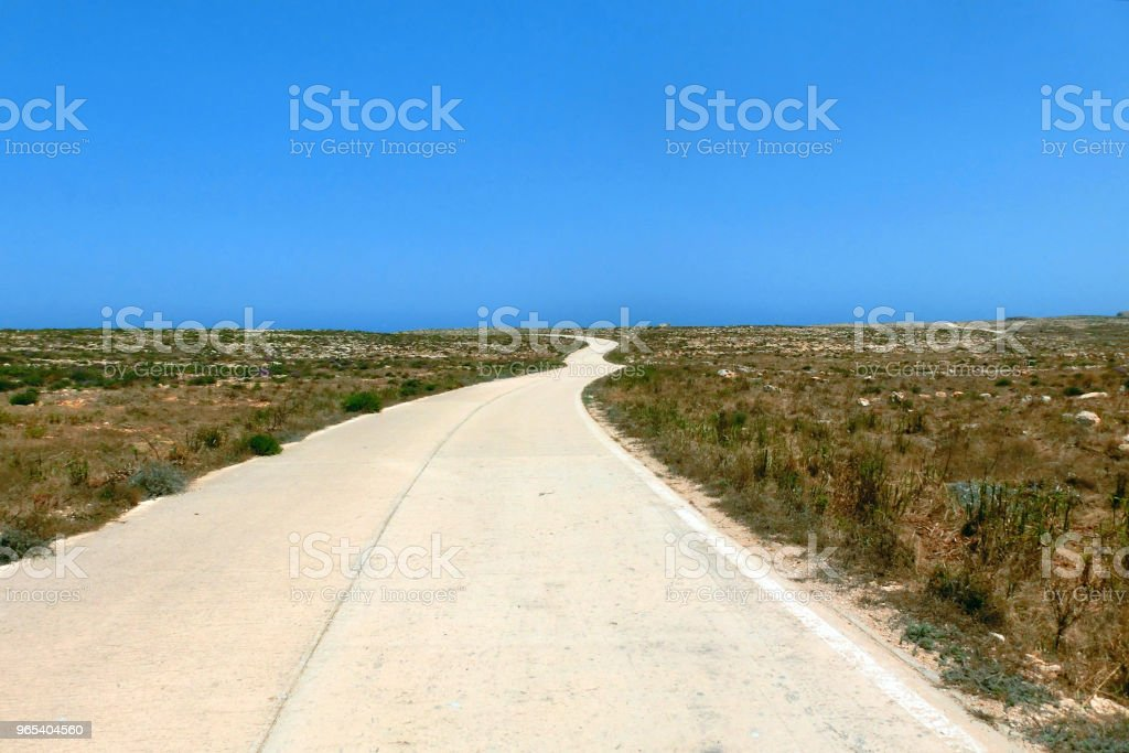 road in the plain leading to the blue sea royalty-free stock photo