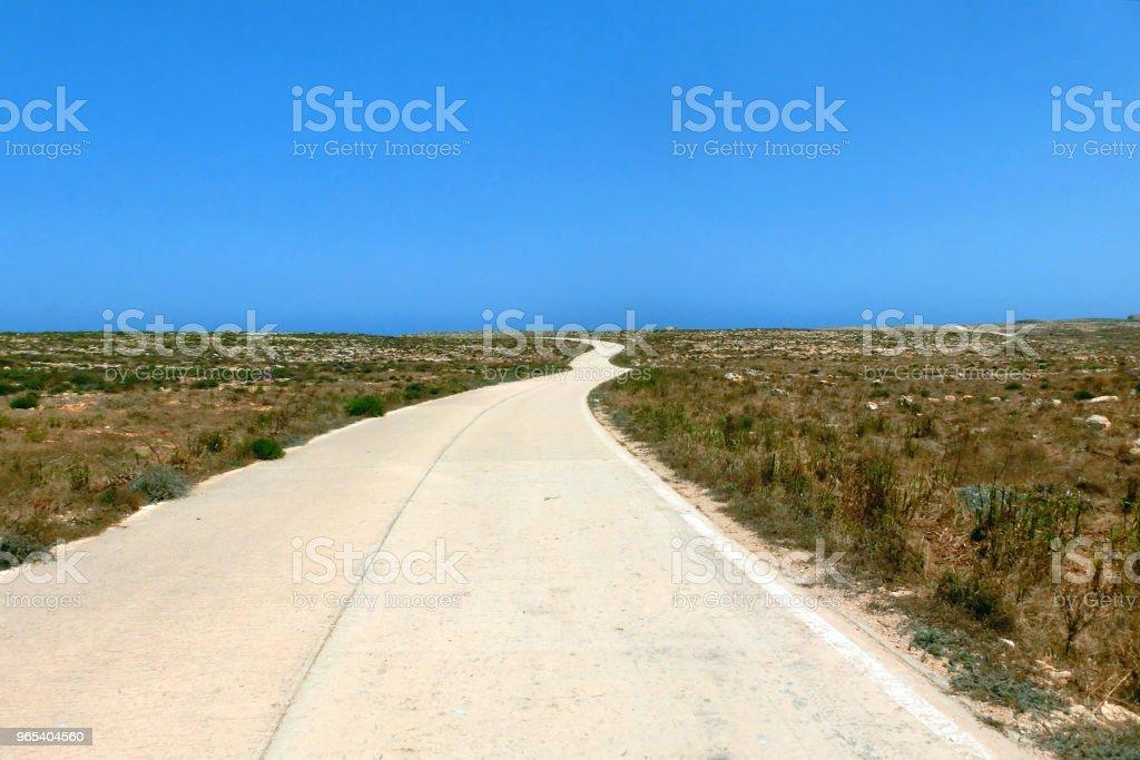 road in the plain leading to the blue sea zbiór zdjęć royalty-free