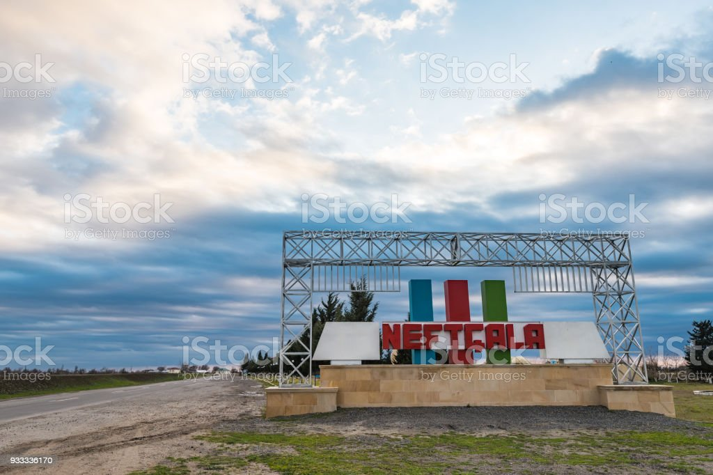 Road in the regions of Azerbaijan, city name on signboard - Neftchala. Translation into English - Neftchala city stock photo
