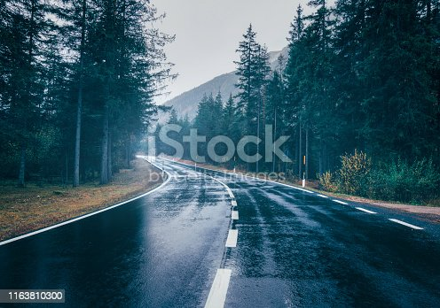 Road in the summer foggy forest in rain. Landscape with perfect asphalt mountain road in overcast rainy day. Roadway with reflection and green trees in fog. Vintage style.  Empty highway. Travel