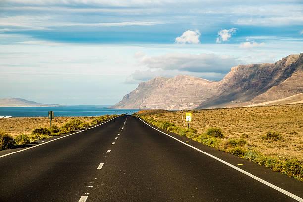 road in the volcanic area of lanzarote - carlosanchezpereyra fotografías e imágenes de stock