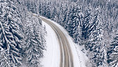istock Road in the winter mountain forest. Drone view. 1336134874