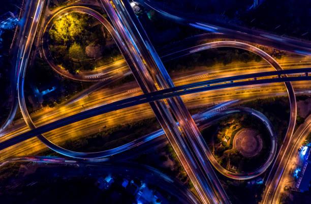 échangeur routier dans la ville la nuit avec le mouvement de lumière de voiture de véhicule, vue aérienne. - rond point carrefour photos et images de collection