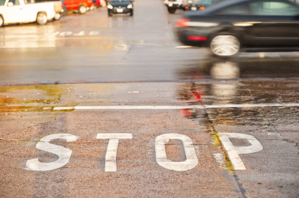 road junction, stop word, motion blurred car in rain and sun - stop motion stock photos and pictures