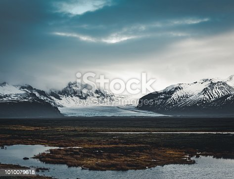 Road leading towards huge glacier and mountains in Iceland Vatnajokull glacier aerial drone image with street highway and clouds and blue sky. Dramatic winter scene of Vatnajokull National Park, Iceland, Europe. Beauty of nature concept background. Photo taken in Iceland