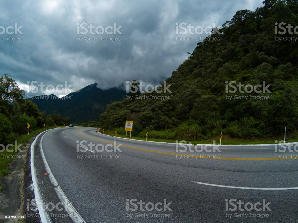 Road, mountains and cloudy sky stock photo