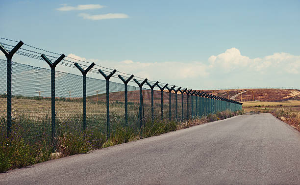 Road next to a fence Road next to a fence in a  clear day. international border barrier stock pictures, royalty-free photos & images