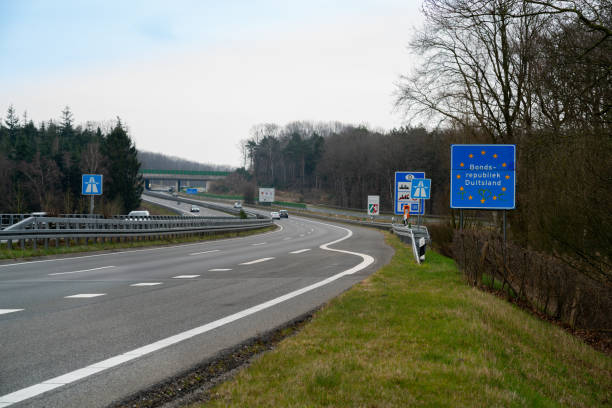 Road of Deutschland border with a sign that reads 'Bondsrepubliek Duitsland' ( Federal Republic of Germany), Europe , Europe  - March 27, 2018:   view showing grass, trees, fences,brige, cars and signs on the street in Deutschland border duitsland stock pictures, royalty-free photos & images