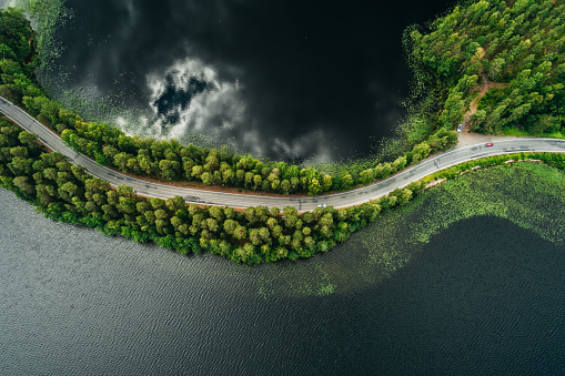 Road on a narrow piece of land between two lakes with forest