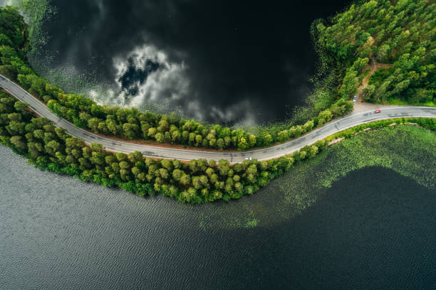 Road on a narrow piece of land between two lakes with forest Road on a narrow piece of land between two lakes seen from the air at Punkaharju ridge Finland narrow stock pictures, royalty-free photos & images