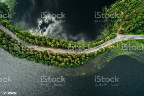Photo of Road on a narrow piece of land between two lakes with forest