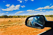 Australian outback red soil and scarse gum-trees under blue sky with rear view mirror through driving car blurring road side.