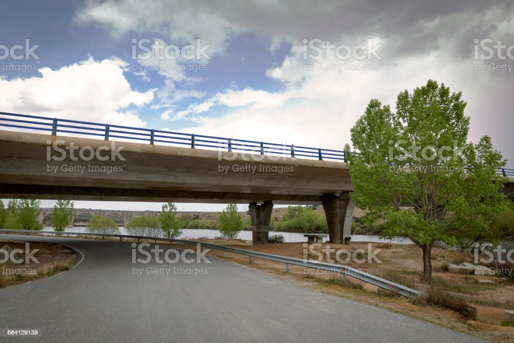 Road passing under a bridge of a highway royalty-free stock photo
