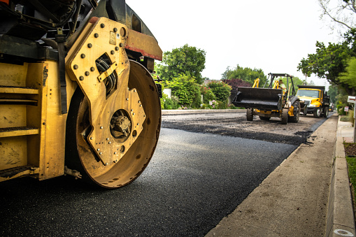 A shot of a road being resurfaced in a residential neighborhood in La Canada, California. Half of the street is paved and the other is unpaved. The machinery is lined up and working together.