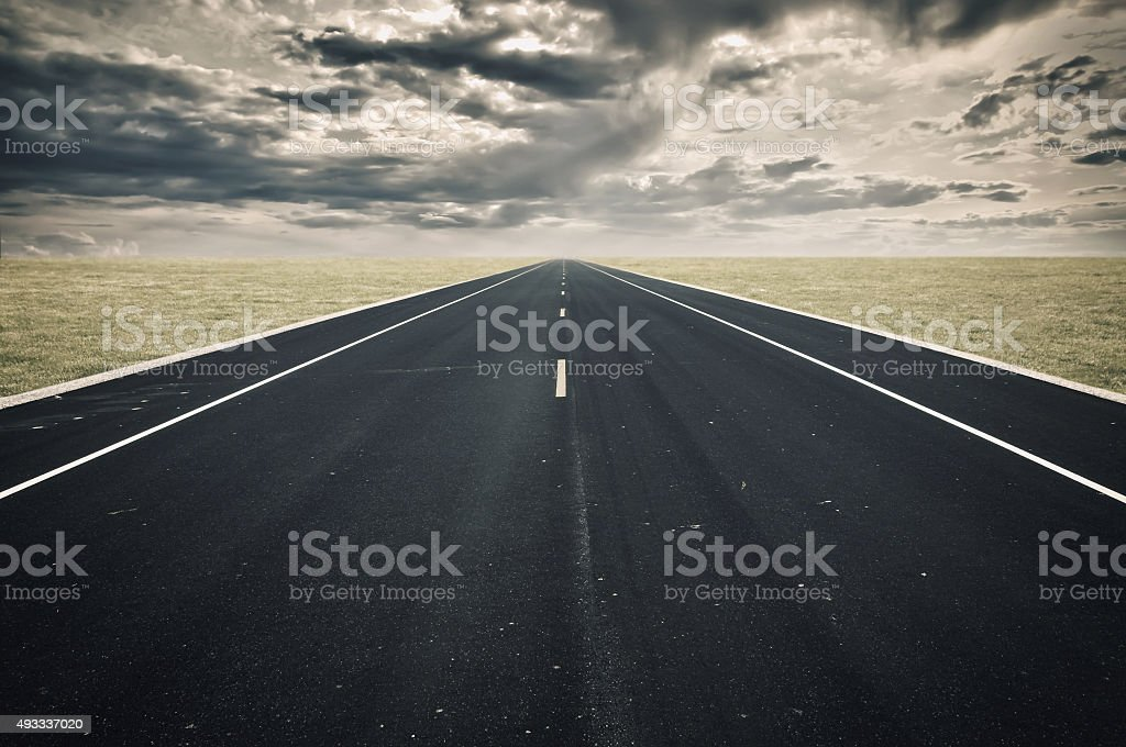 Road perspective, dark clouds, crisis concept stock photo