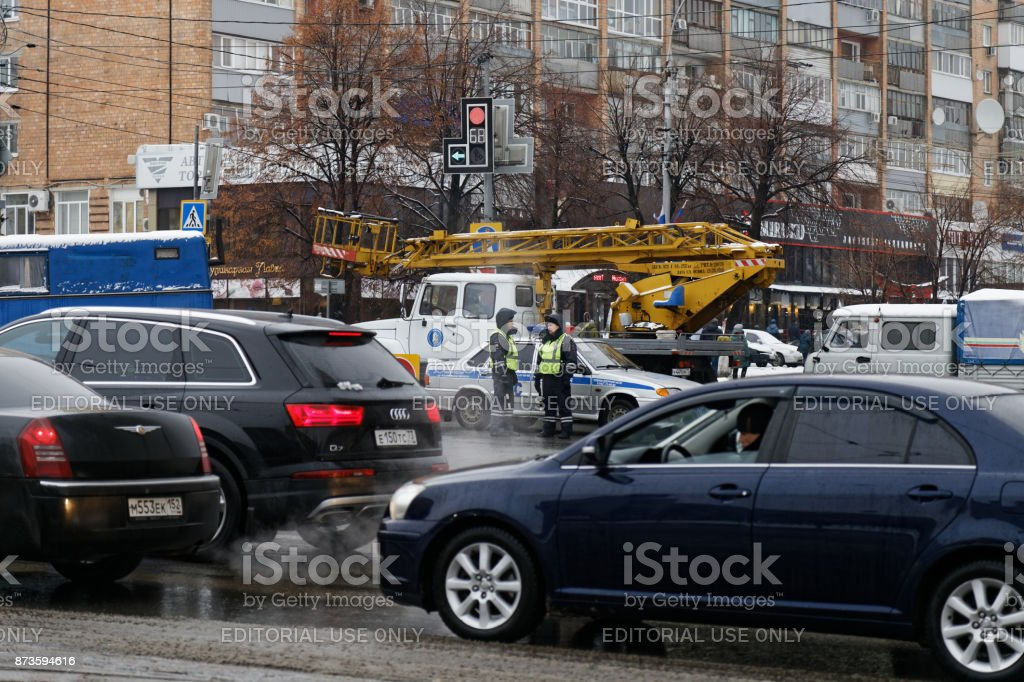 Road policemen stand on a city street among cars passing by stock photo