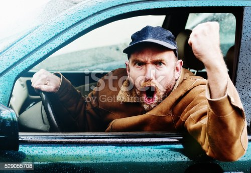 istock Road rage: Furious male driver yelling, shaking fist through window 529055708
