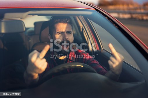 Front view image of young frustrated man shouting and making obscene gesture as he drives