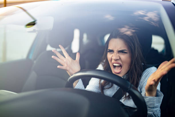 Road rage traffic jam concept Closeup portrait, angry young sitting woman pissed off by drivers in front of her and gesturing with hands. Road rage traffic jam concept. Woman is driving her car very aggressive and gives gesture with his fist displeased stock pictures, royalty-free photos & images