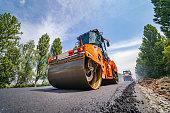 istock Road repair, compactor lays asphalt. 1203126594