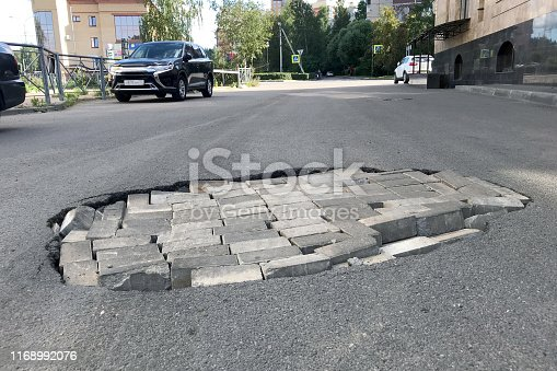 istock Road repair concept. Closeup of a pit with a brick in an asphalt road. Buildings and parked cars 1168992076