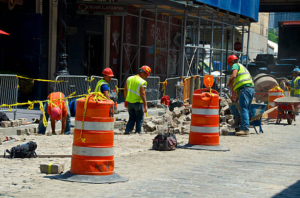 Road repair workers in Lower Manhattan, New York City New York City, USA - June 20, 2013: A Road repair crew of workers replacing cobblestone blocks on a street in Lower Manhattan. south street seaport stock pictures, royalty-free photos & images