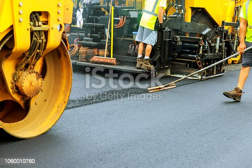 Road roller at a road construction site, paver laying fresh asphalt pavement during road