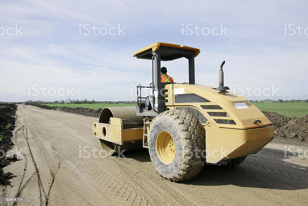 Road roller preparing the substrate on a new highway project royalty-free stock photo