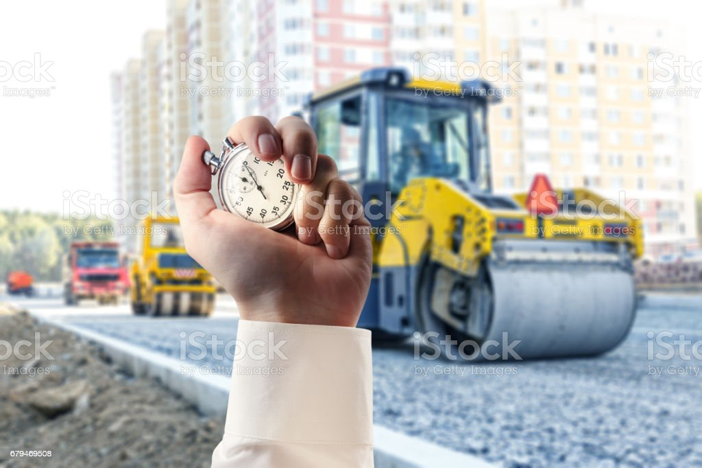 Road roller working and stopwatch in hand 免版稅 stock photo