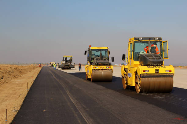 Road rollers leveling fresh asphalt pavement on a runway TULCEA, ROMANIA - NOVEMBER 08: Road rollers leveling fresh asphalt pavement on a runway as part of the Danube Delta international airport expansion plan on November 08, 2015 in Tulcea, Romania. compactor stock pictures, royalty-free photos & images