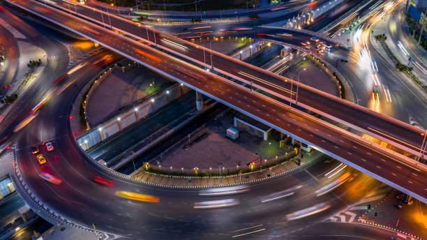carrefour rond-point de la route dans la ville la nuit avec le mouvement de lumière de voiture de véhicule, vue aérienne. - rond point carrefour photos et images de collection