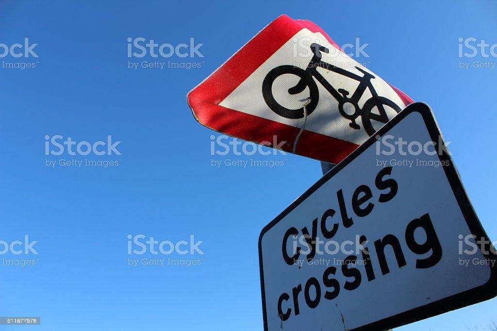 Damaged, bent cycling sign. Sign depicting warning cycles crossing....