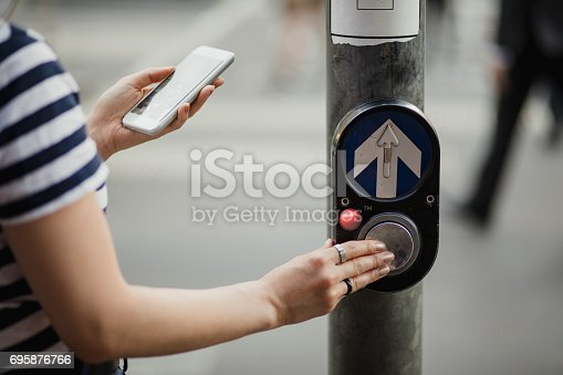 Close-up shot of a young woman pushing the button on a crosswalk.
