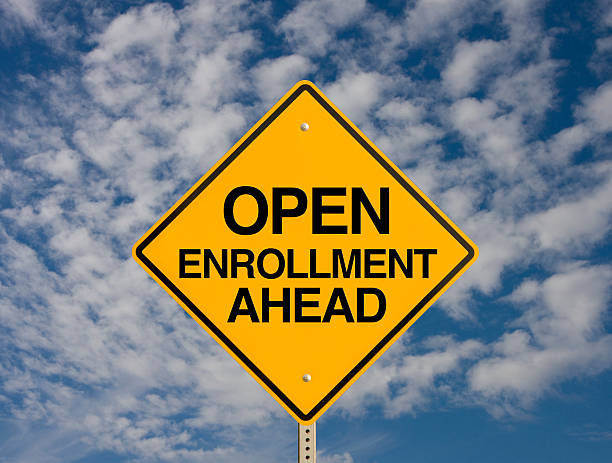 road sign against sky background stating open enrollment - open enrollment stock photos and pictures