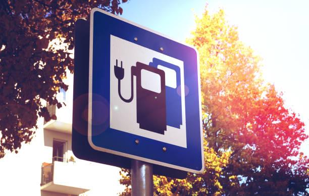 road sign for electric vehicle charging stations - macchina ibrida foto e immagini stock