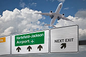 Road sign indicating the direction of Hartsfield-Jackson airport and a plane that just got up.
