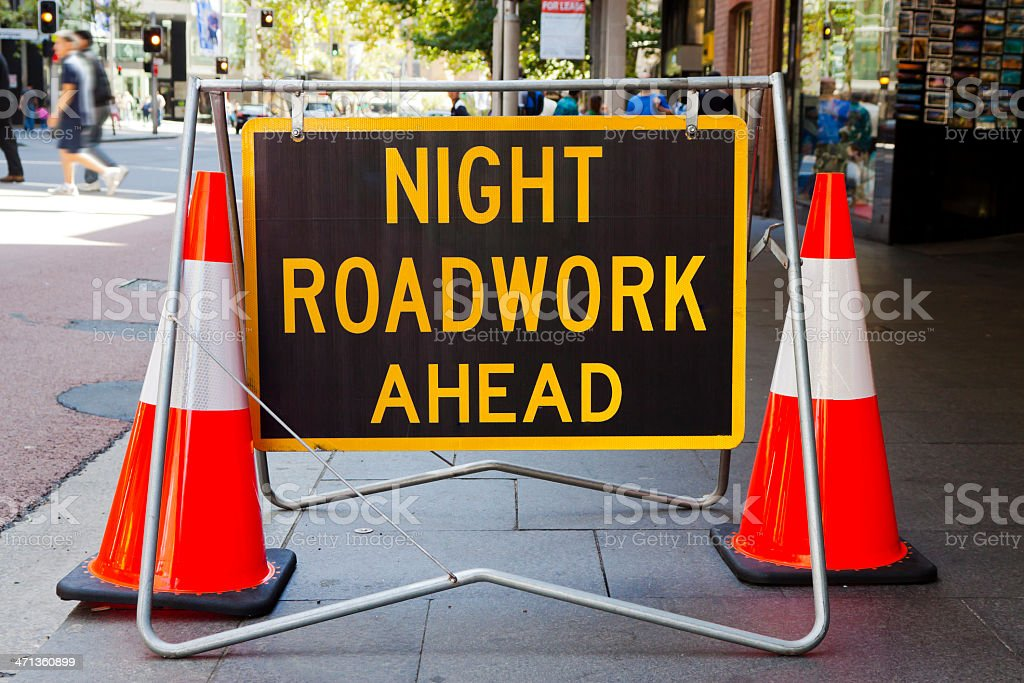 Road sign 'Night roadwork ahed' and two red cones royalty-free stock photo